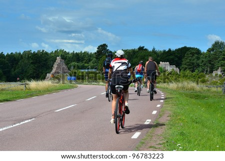 group of cyclists going on the road in the countryside