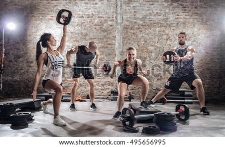 Group of fit and muscular people practicing with barbell on urban place  #495656995