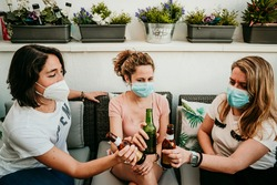 Group of girlfriends meeting after the quarantine caused by the covid19. Taking precaution with the use of surgical masks and toasting with beer for the reunion. New normal