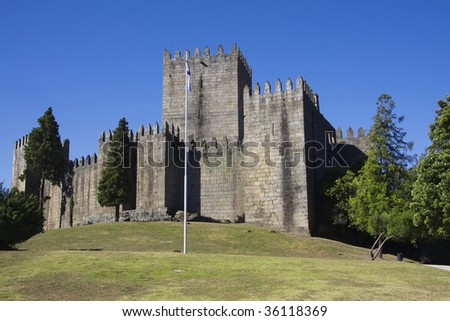 Guimaraes castle in the north of Portugal  and surrounding park against a clear blue sky
