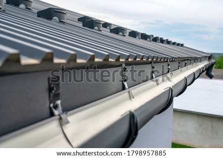 . Gutter system for a metal roof. Holder gutter drainage system on the roof. Stockfoto ©