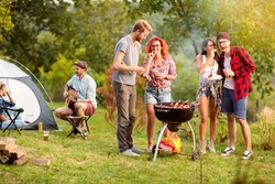 Guys and lassies feed each other with skewers in outing in wood