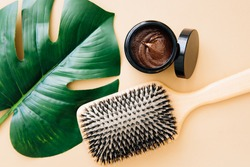 Hair care concept. Wooden comb and natural hair mask lie on beige background. Spa care. Hair treatment.