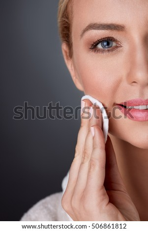 half portrait of middle-aged woman cleaning skin on face