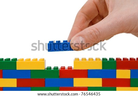 hand building up a wall by stacking up lego. - stock photo