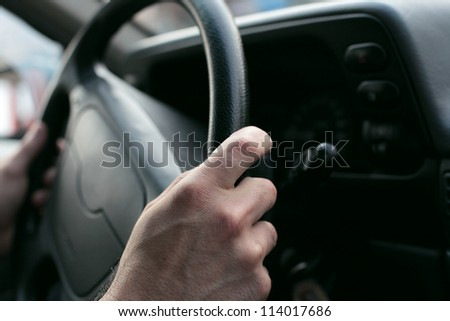 hand close up of a man driving a car