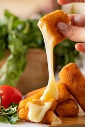 Hand grabbing Mozzarella stick with tomato