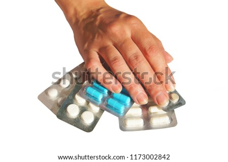 Hand holding assortment of  physic pills on a white background