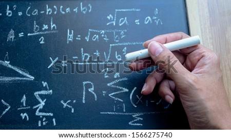 ็ืHand  holding chalk Write mathematical formulas on the blackboard. Concept Difficult problem or Solving mathematical problems.