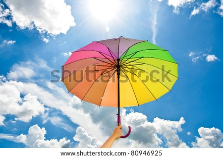 hand holding multicolored umbrella against the sunny sky