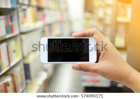 - hand holding phone on blurred bookstore as background