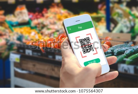 Hand holding smartphone to scan QR code payment , online shopping , cashless technology concept.  #1075564307