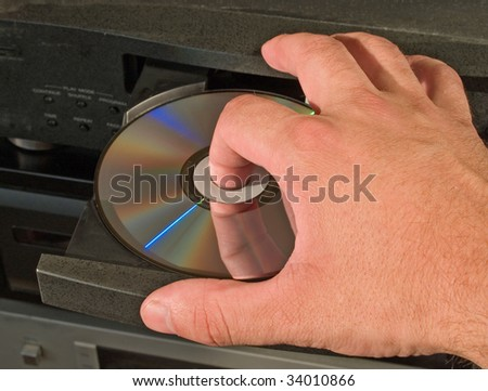 hand inserting musical disk in player