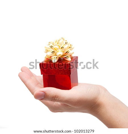 hand is holding single red gift box with silver-beige ribbon. Isolated on white background with clipping path