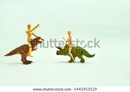 Hand movements of dolls climbing toy dinosaurs.                               #1445953529