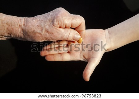 hand of grandmother and grandchild with a pill