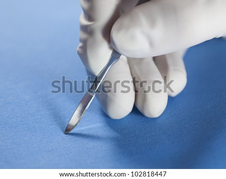 Hand of the surgeon in a glove, holding a scalpel.