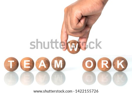 """Hand putting on Wooden ball with word """"TEAMWORK"""", The concept of teamwork bundles to victory"""