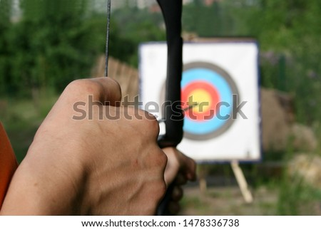 hand, stretching a bow and aiming the target in the background #1478336738