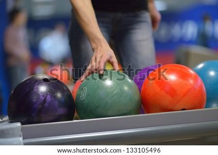 Hand taking ball from bowling ball machine