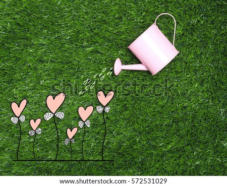 hand  watering love heart  trees  on color background and top wood table for Christmas and The New Year and Valentine's day .Decoration love heart and drawing free hand cartoon cute love. #572531029