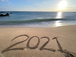 2021hand written in sand on beautiful beach background.