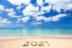 2021 hand written sign on sandy beach