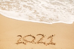 2021 hand written sign on sandy beach with waves and white foam. Happy New year 2021 ! Welcoming 2021 with new resolutions, dreams, lists