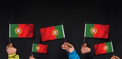 Hands hold flags of Portugal on dark background