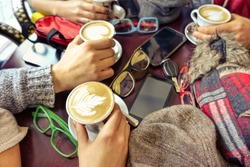 Hands holding cappuccino cup interior scene - Group of friends drinking coffee in bar cafe restaurant - Concept of friendly business meeting with trendy milk drinks and mobile phone on table