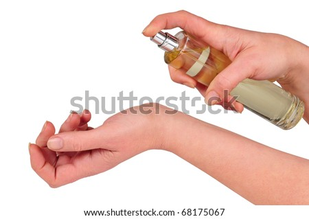"""hands holding flask of perfume and pulverizing it in the doll   """