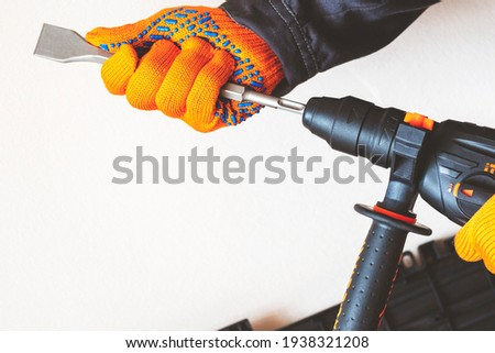 hands in protective gloves, hammer drill, installation of a chisel in a perforator. The concept of replacing the rotary drill.close-up. Stock photo ©
