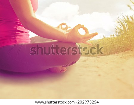 hands of a woman meditating in a yoga pose on the beach done with an instagram like filter