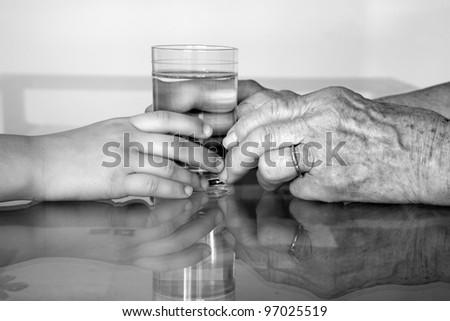 hands of grandmother and grandchild with the glass of water