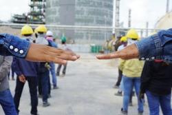็Hands of the workers unfolded to measure the distance during line up to safety talk or toolbox talk at Chemical plant in construction area. Corona virus epidemic. (Covid 19)