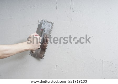 Hands Plasterer at work. Application of the plaster on the wall. textured plaster