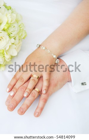 stock photo 2 hands with wedding rings and flowers
