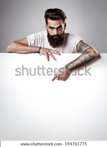 Handsome bearded man holding blank poster