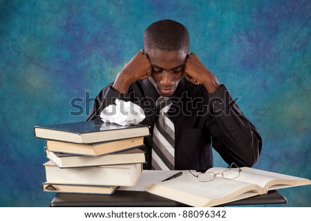 Handsome black man thinking and contemplating what he has read in a book with a depressed look