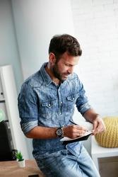 Handsome businessman sitting on a desk, writing notes. Businessman making businessplan..