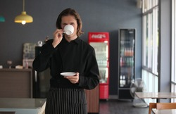 Handsome male barista is working in coffee shop