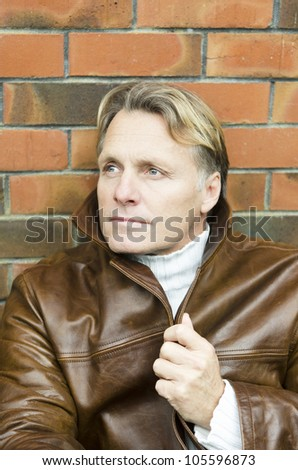 ... handsome mature blond man in his forties wearing a brown leather jacket.