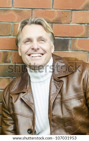 handsome mature blond man in his forties wearing a brown leather jacket. - stock photo