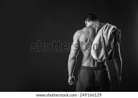 Handsome, muscular man in sportswear posing on a dark background. Confident man in an unbuttoned jacket. Bodybuilder man in  sports jacket.
