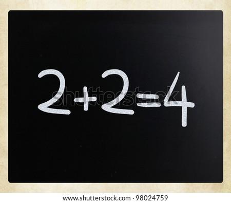 """2+2=4"" handwritten with white chalk on a blackboard"