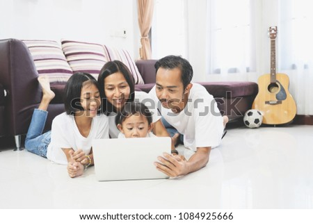 Happy asian family and little daughter are lying on a floor at home and using a laptop computer