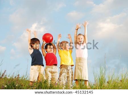 happy children raising hands upwards