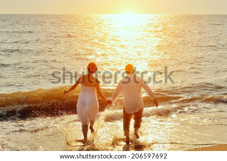 happy couple running to the sea on the beach at sunset #206597692