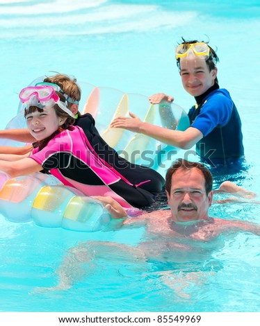 Happy family playing in pool