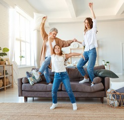 happy family three generations   grandmother, mother and child dancing, jumping and laugh at